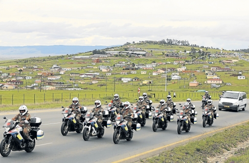 Military outriders ride past a village as they rehearse escorting the funeral cortege for former South African President Nelson Mandela through the streets in Mthatha