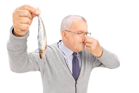 31619002-senior-gentleman-holding-a-rotten-fish-isolated-on-white-background